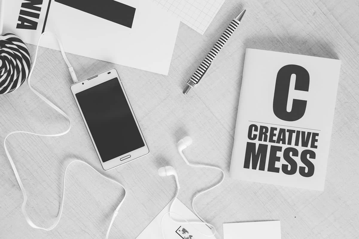 """A desk is covered in black and white design tools, including a smartphone, pen, and card that says """"Creative Mess."""""""