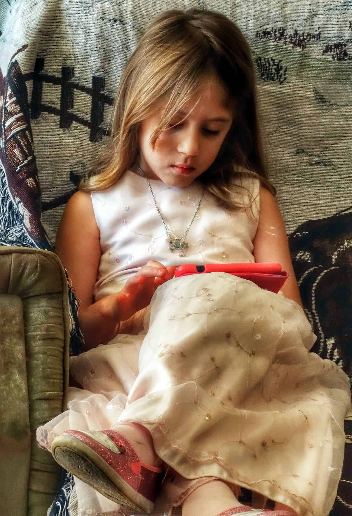 A photo of a young girl using an iPad, demonstrating one of the greatest benefits of accessible mobile UI design: an expanded, more diverse audience for your app.