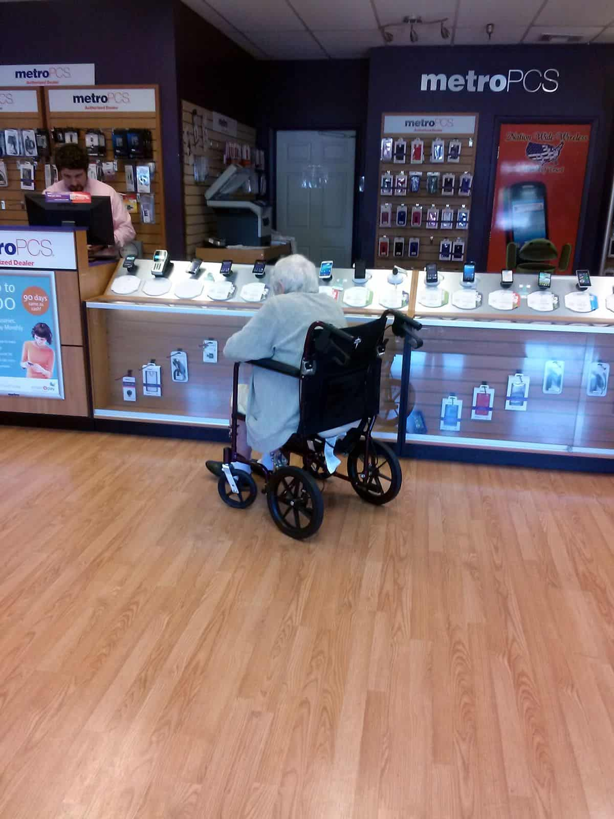 A senior citizen in a wheelchair chooses between several smartphones to purchase.