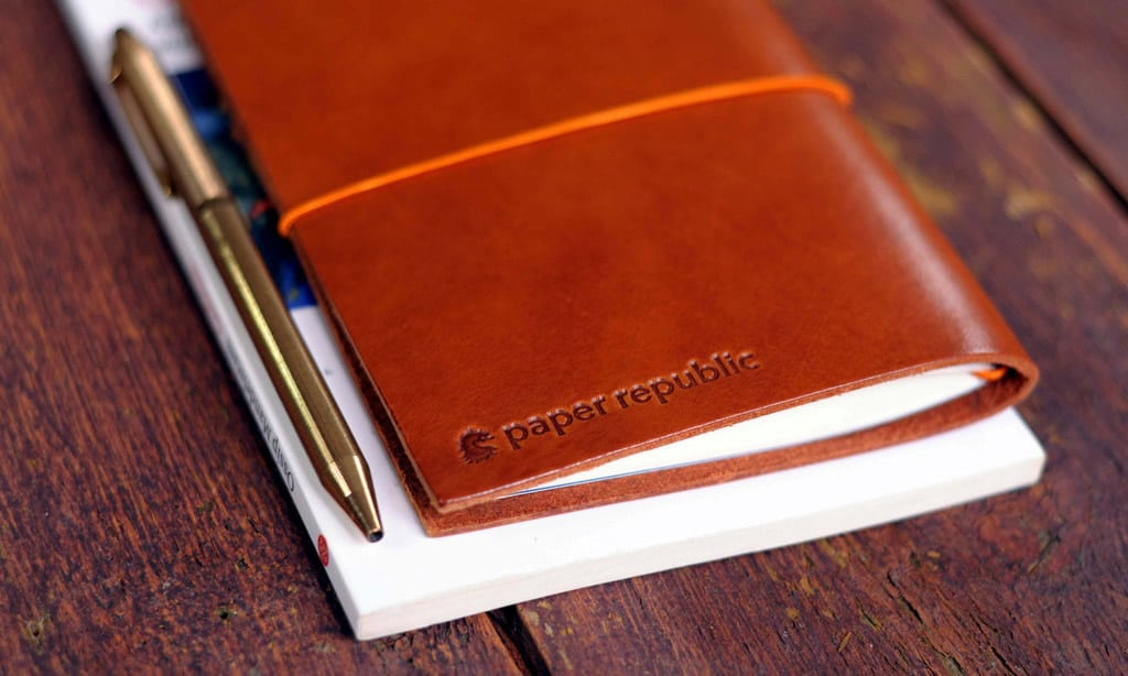 Brown leather cover bearing the name Paper Republic, holding a notebook within and a golden pen.