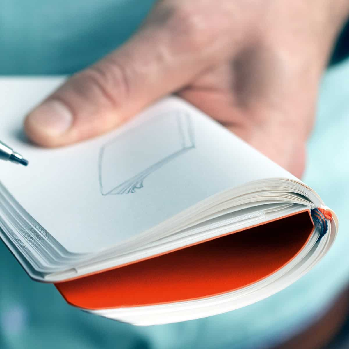 Close-up of a hand holding an opened Notebook Pocket A6 with a drawing of a notebook on the page.