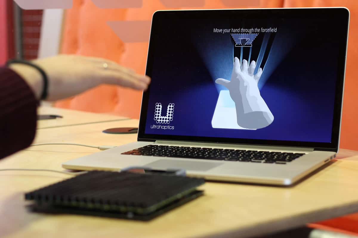 A photo of a person's hand moving through an invisible forcefield of sound waves during a demonstration of Ultrahaptics' product.