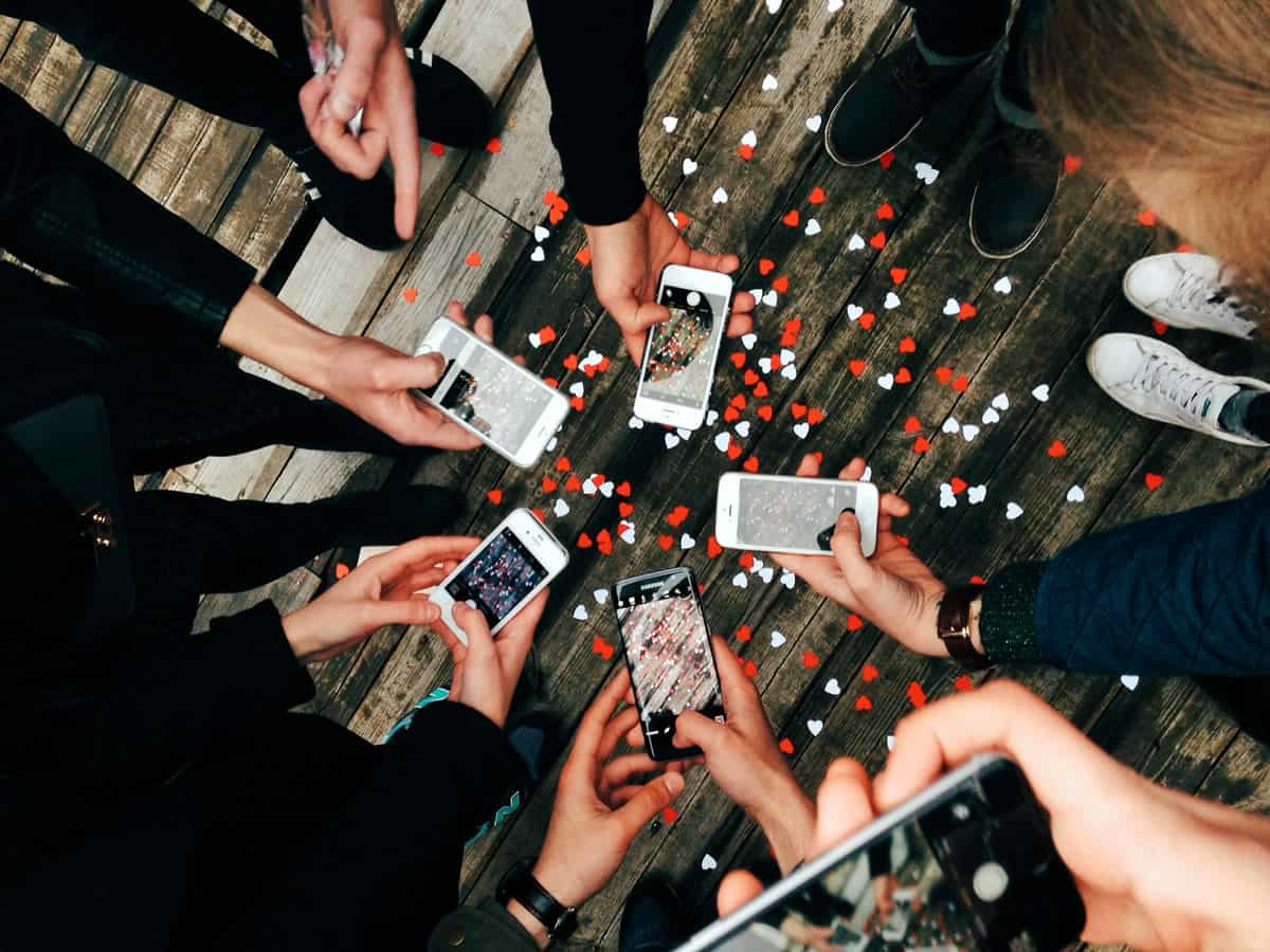A photo of seven people in a circle using their mobile devices to take pictures.