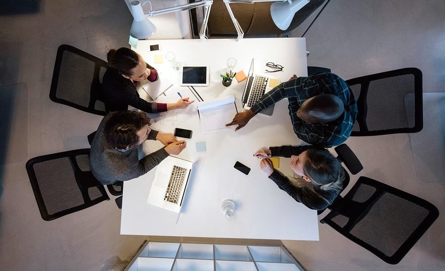 A photo from above of four people working together around a white table.