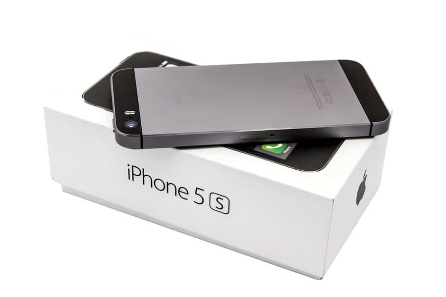 A photo of the iPhone 5S in space gray face down on its box.