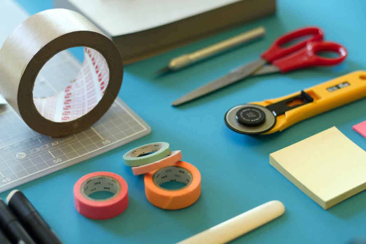 Image of tools on a table including tape, sticky notes, and scissors