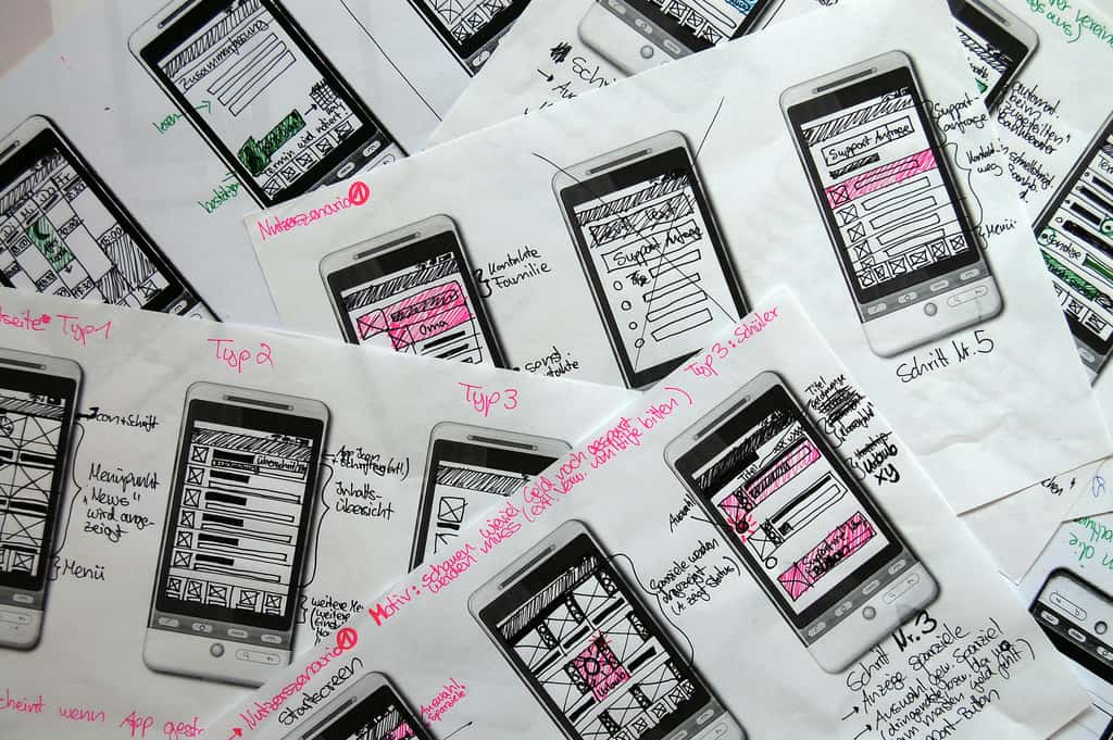 Image of a pile of mobile template papers filled with wireframes created with black and pink pens.