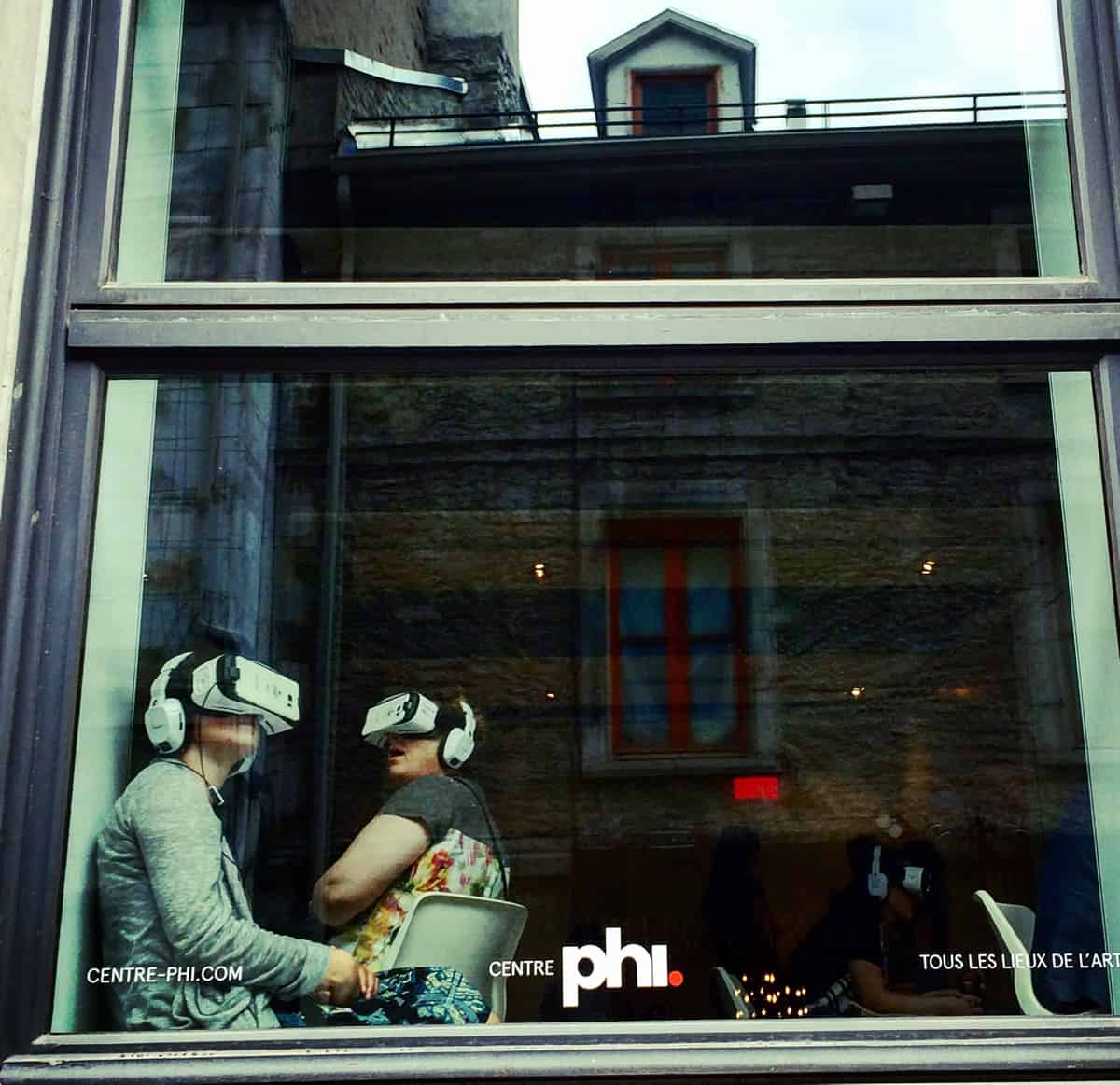 A photo of a couple sitting in a storefront window, each wearing head-mounted virtual reality goggles.