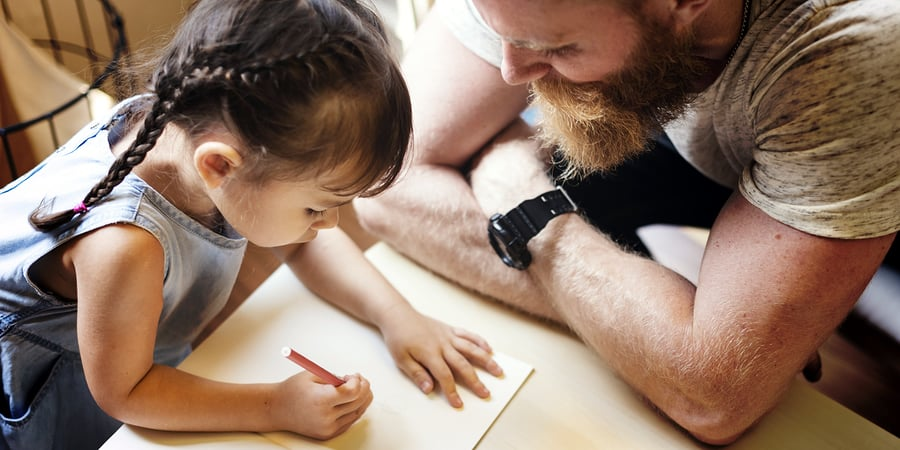 A photo of a father and daughter sitting down to draw.