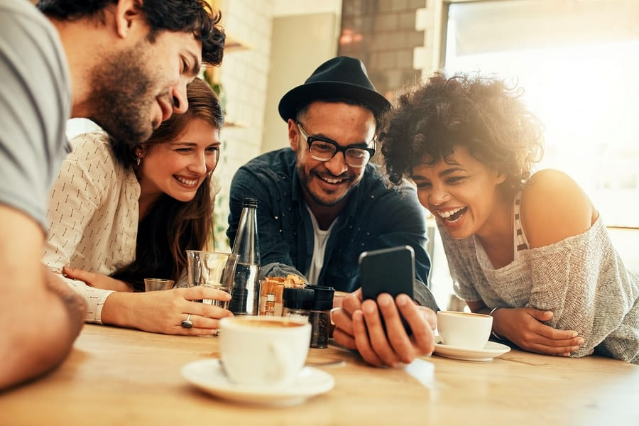 A photo of four people smiling and laughing gleefully at something on a smartphone.