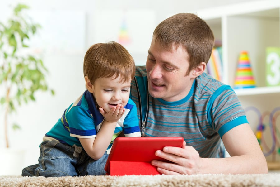 A photo of a father and son playing a game on a tablet.