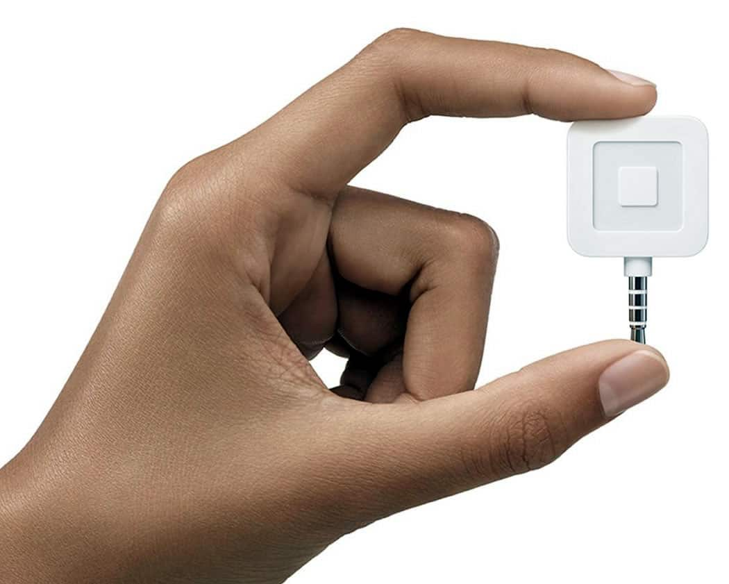 Image of a hand holding a square reader.
