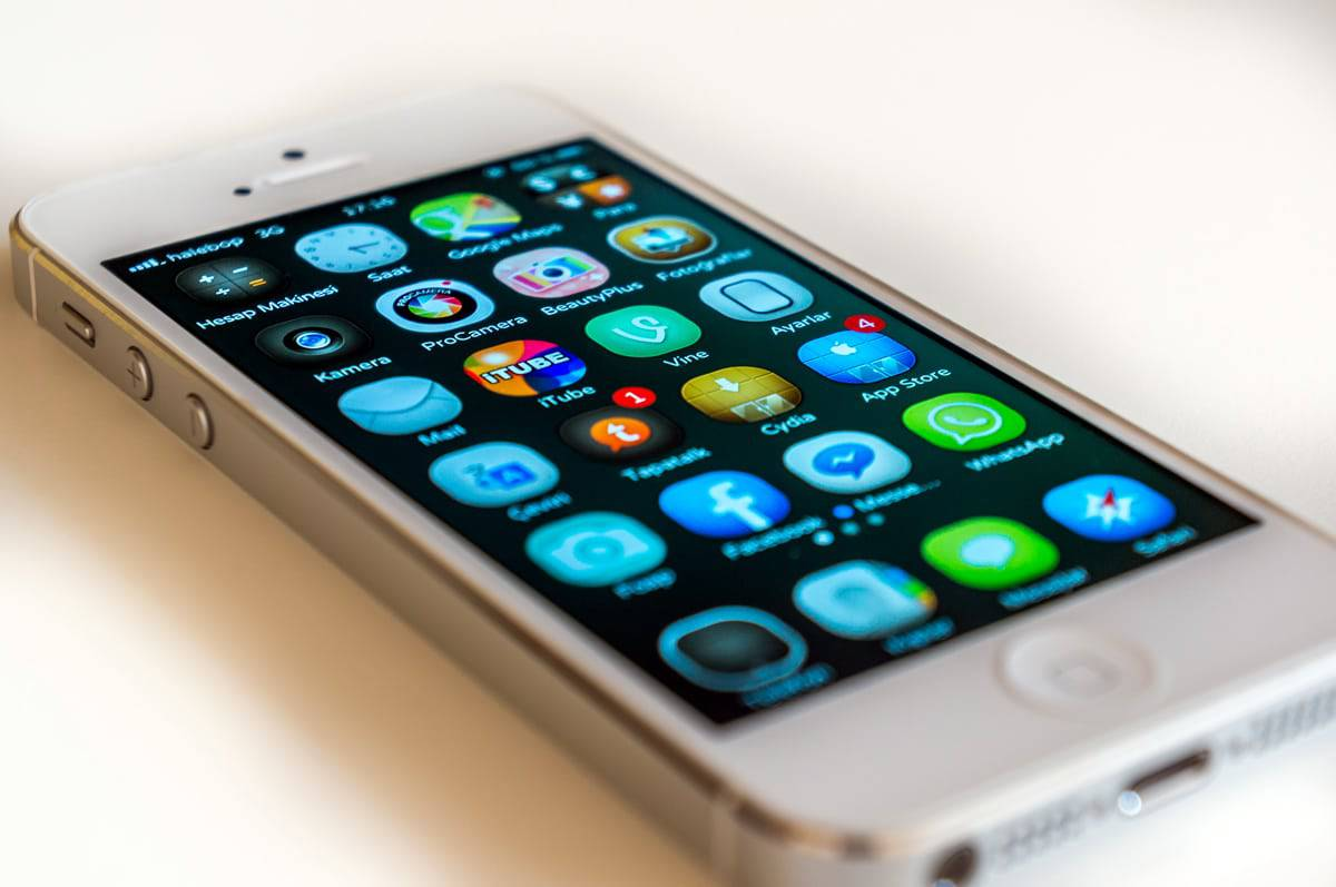 A photo of an iPhone screen with multiple mobile app icons displayed.