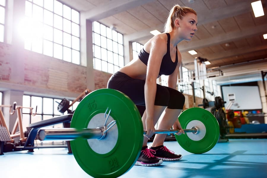 A photo of a woman preparing to do a deadlift with a large barbell and extra weights.