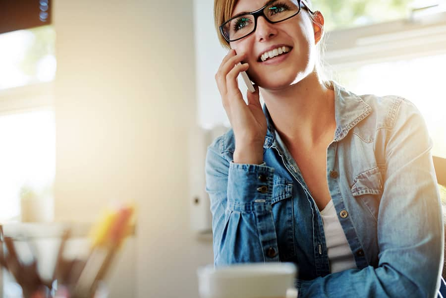 A photo of a woman smiling while talking on the phone with a customer.
