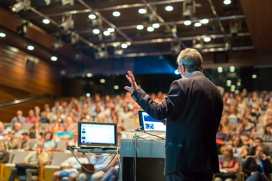 A photo of a man giving a presentation to a large group of people.