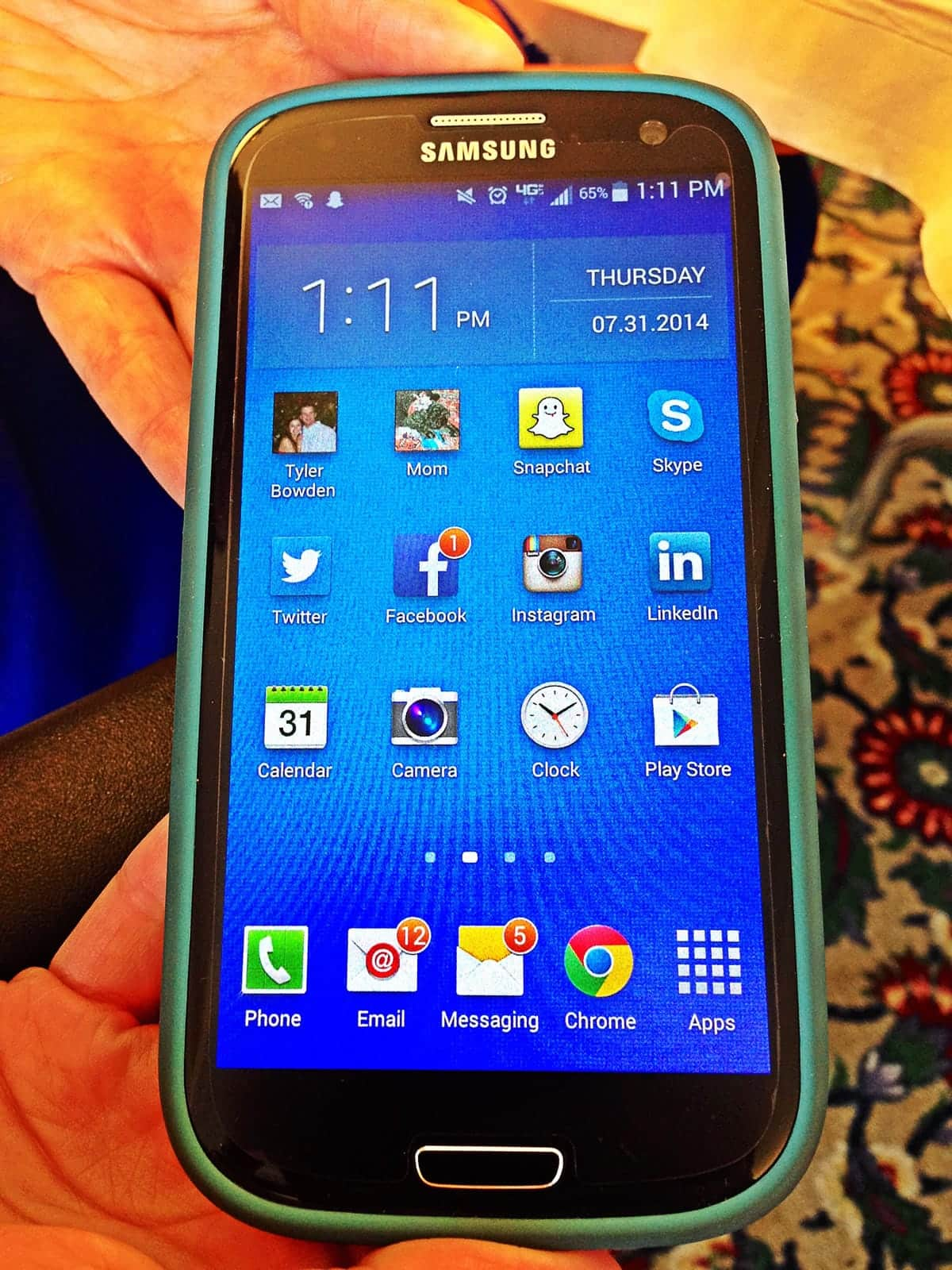 A photo of a person holding a Samsung smartphone displaying the home screen.