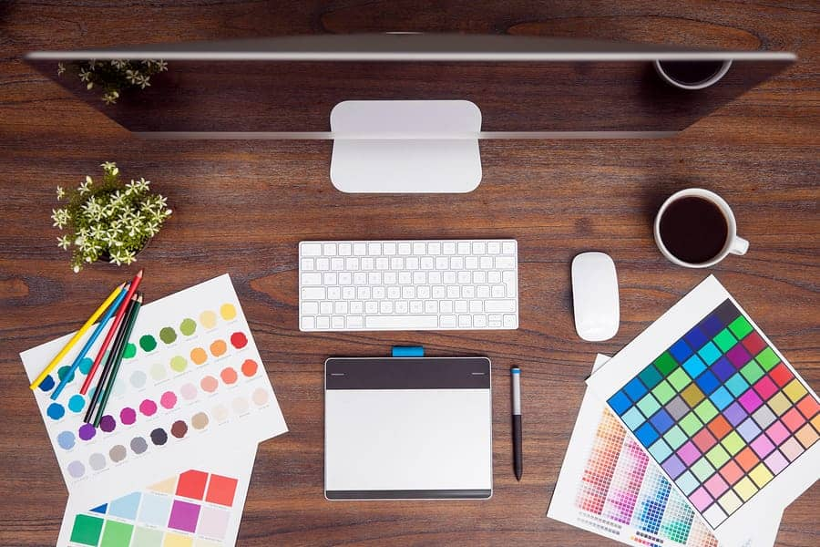 A photo of a designer's desk, complete with color charts, a computer, and a drawing tablet.