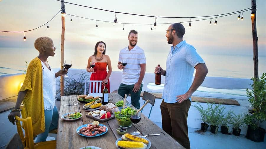 A photo of four people having an outdoor dinner party.