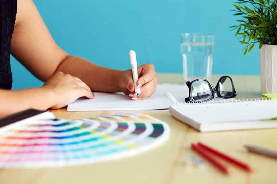 A photo of a graphic designer whipping up some sketches with a color fan spread out next to her.