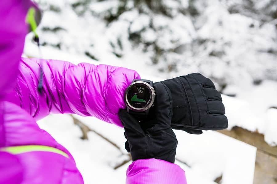 A photo of a woman checking the elevation on her smartwatch during a snowy hike.