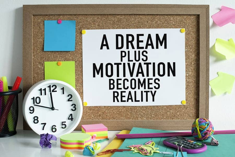 "A photo of a corkboard with a motivational message, saying ""A dream plus motivation becomes reality."""