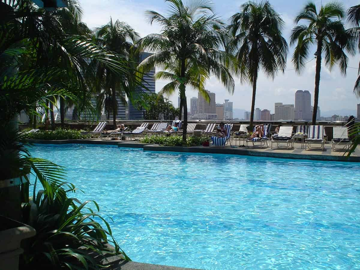 A photo of a gorgeous pool overlooking a city skyline on a warm summer day.