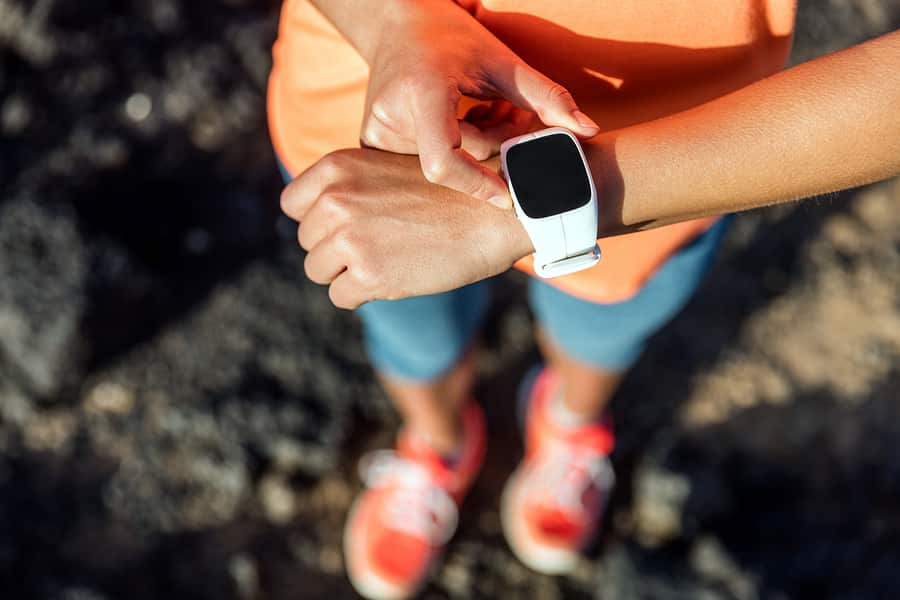 A photo of a woman checking her wearable prior to starting a run.
