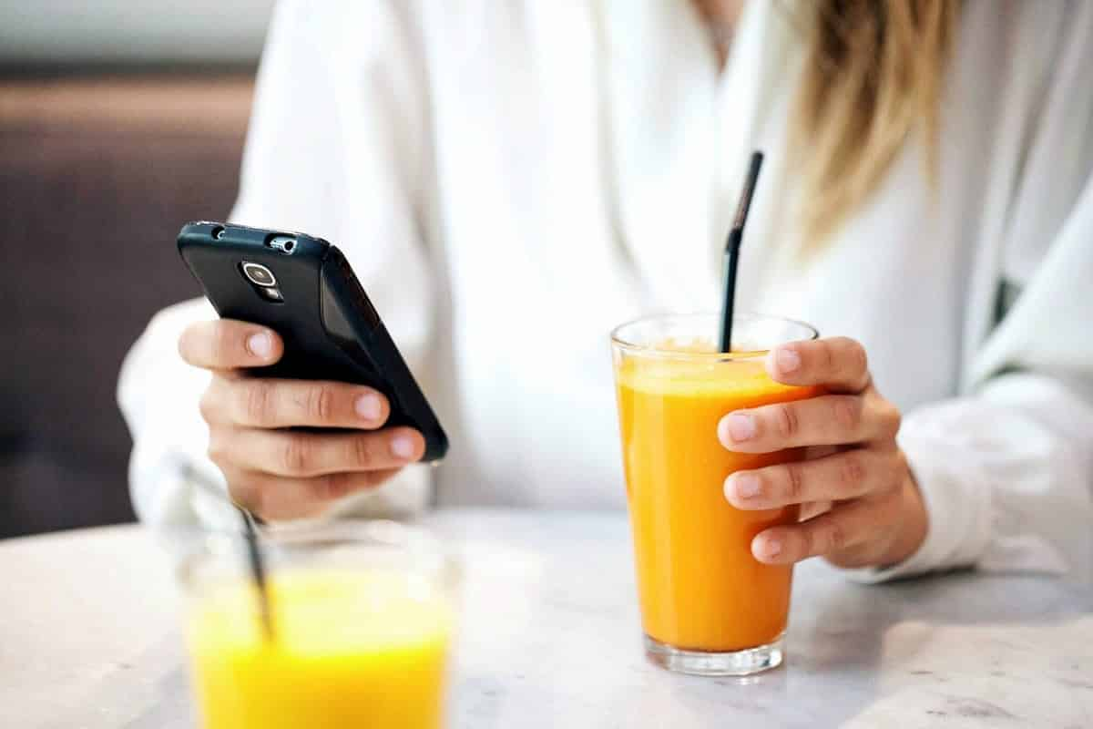 A photo of a woman checking her smartphone over a morning smoothie.