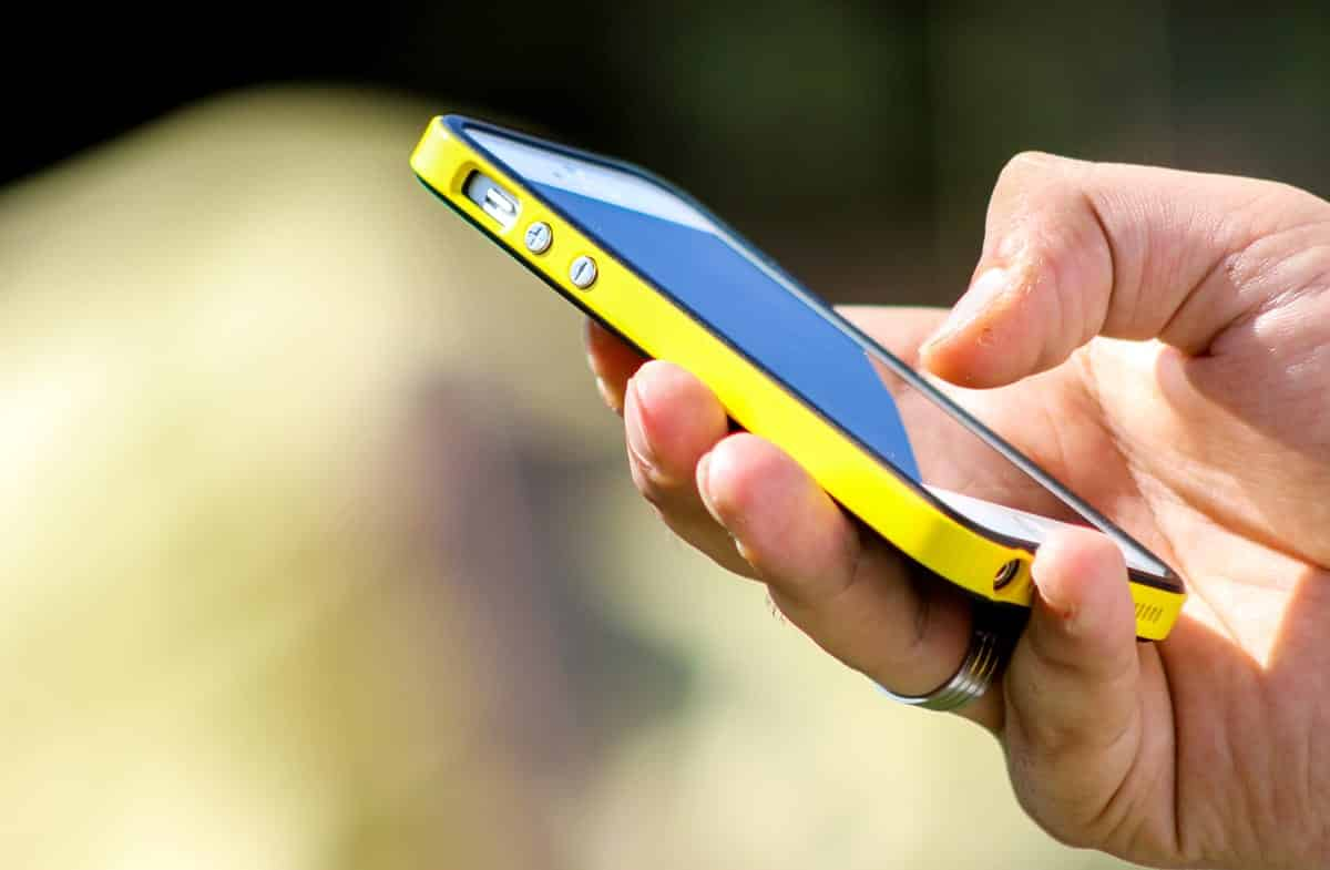 A photo of a person holding an iPhone in a bright yellow case.