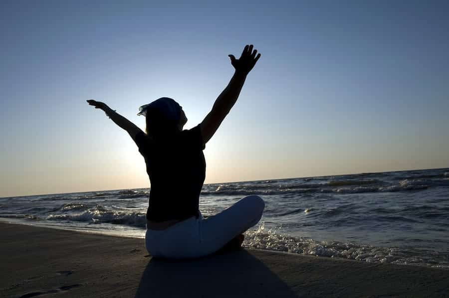 A photo of a woman meditating on a beach at sunrise.