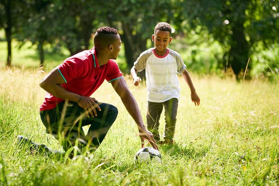 A photo of a dad helping his son learn how to play soccer.