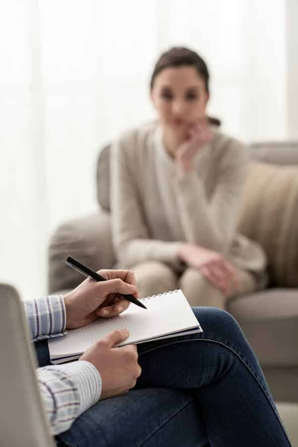 A photo of a therapist taking notes during a session with a patient.