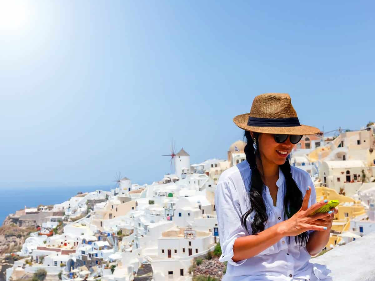 A photo of a woman looking at her smartphone while on vacation in the Mediterranean.