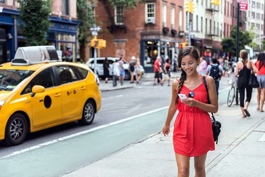 A photo of a woman looking at her phone as she walks down a busy city street.