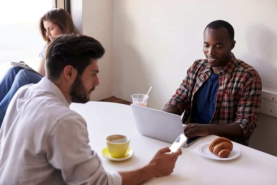A photo of three people sitting near each other, but working separately in a coffee shop.