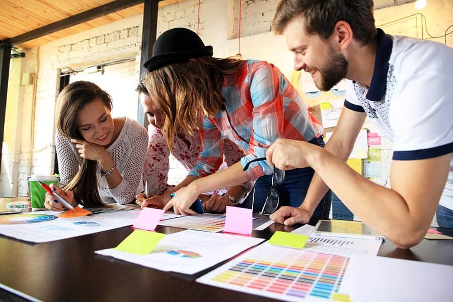 A photo of a design team leaning over color charts.