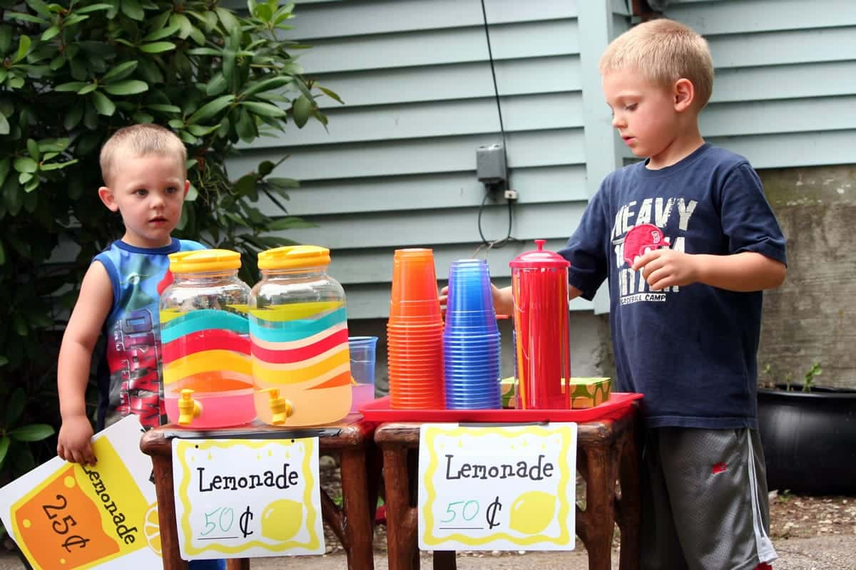 A photo of two young boys setting up a lemonade stand.