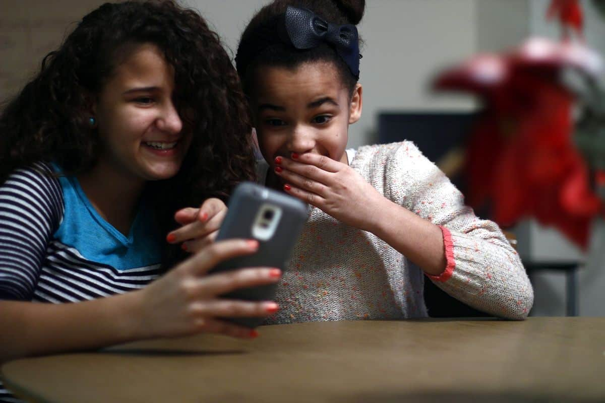 Two young girls laugh while looking at a smartphone, one pointing at the app and the other covering her mouth in surprise.