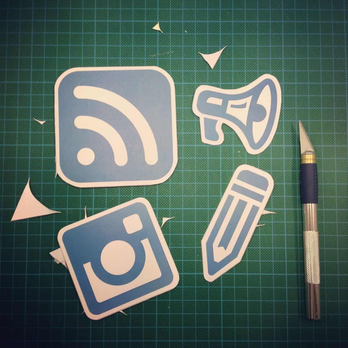 Paper cut-outs of simple flat design icons, all in the same shade of steel blue.