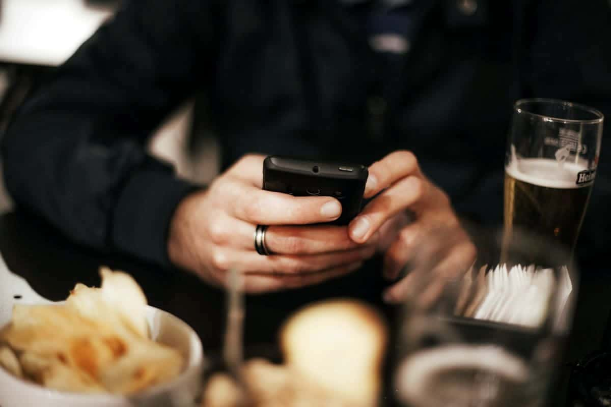 Mobile user tapping on phone while at dinner