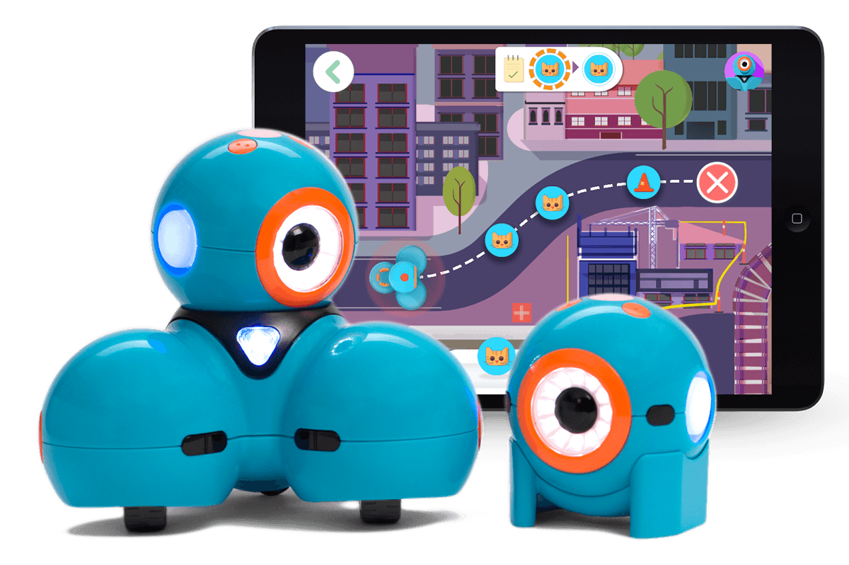 A photo of Dash and Dot, two small, blue, cylindrical robots, each with one big eye, in front of a screenshot of an iPad app showing a cartoon cityscape.