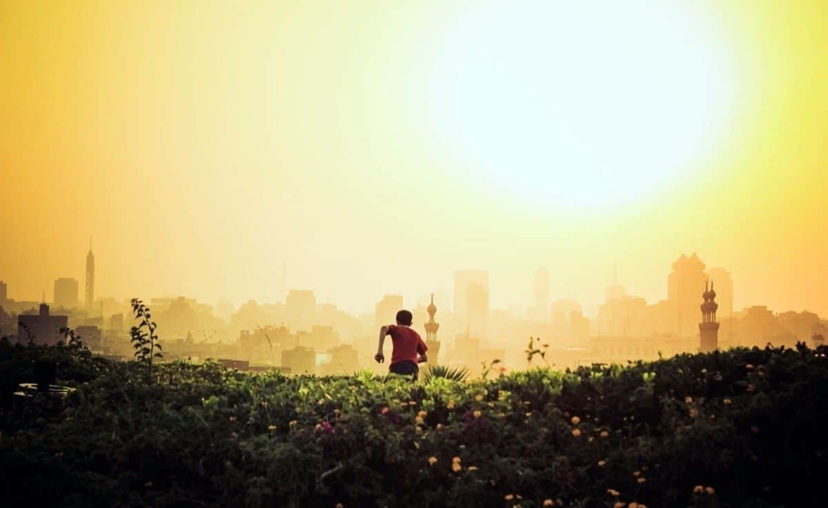 Young boy running in the fields with city and sun as backdrop. The first of all mobile prototyping best practices is to make it fast.