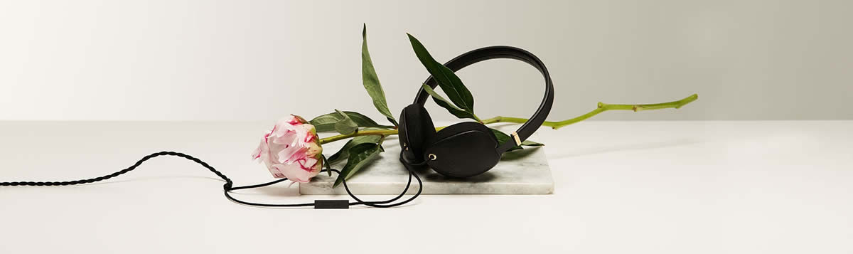 Plica stylish headphones in black laid out next to a pink rose.