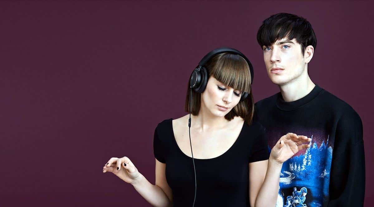 Young woman listening to music with the BeoPlay H6 in black and a young man standing next to her facing the camera