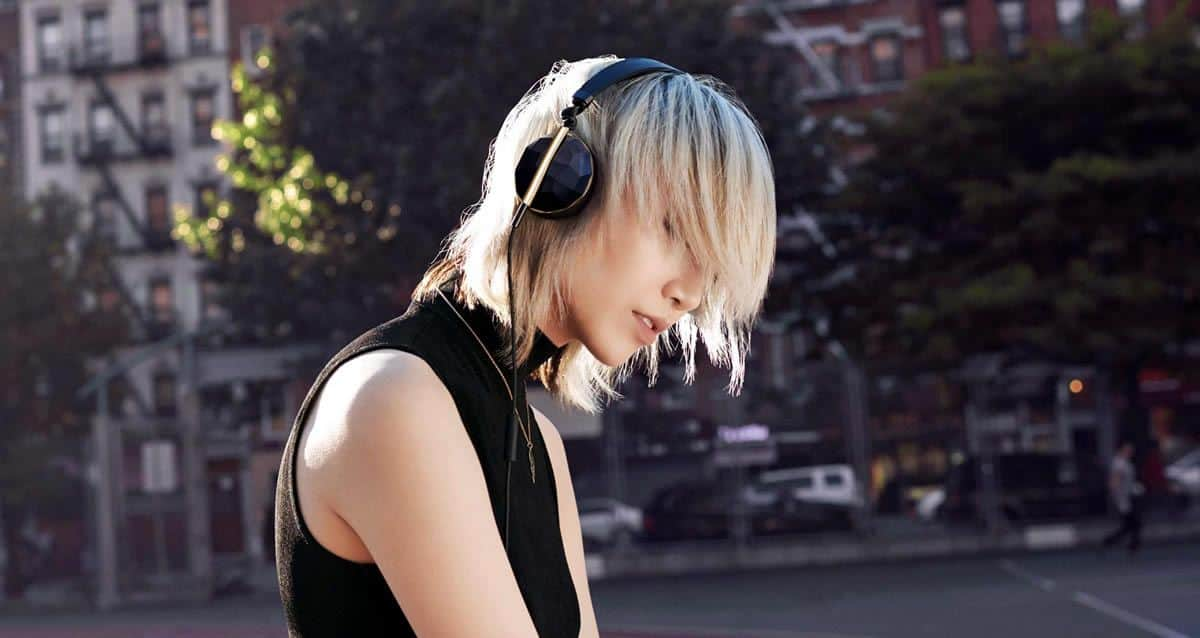 Sideview of a young woman listening to music and enjoying with the black edition of the Linea N1 by Caeden