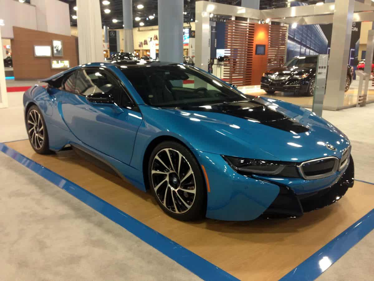 A gleaming blue BMW i8 parked in a showroom.