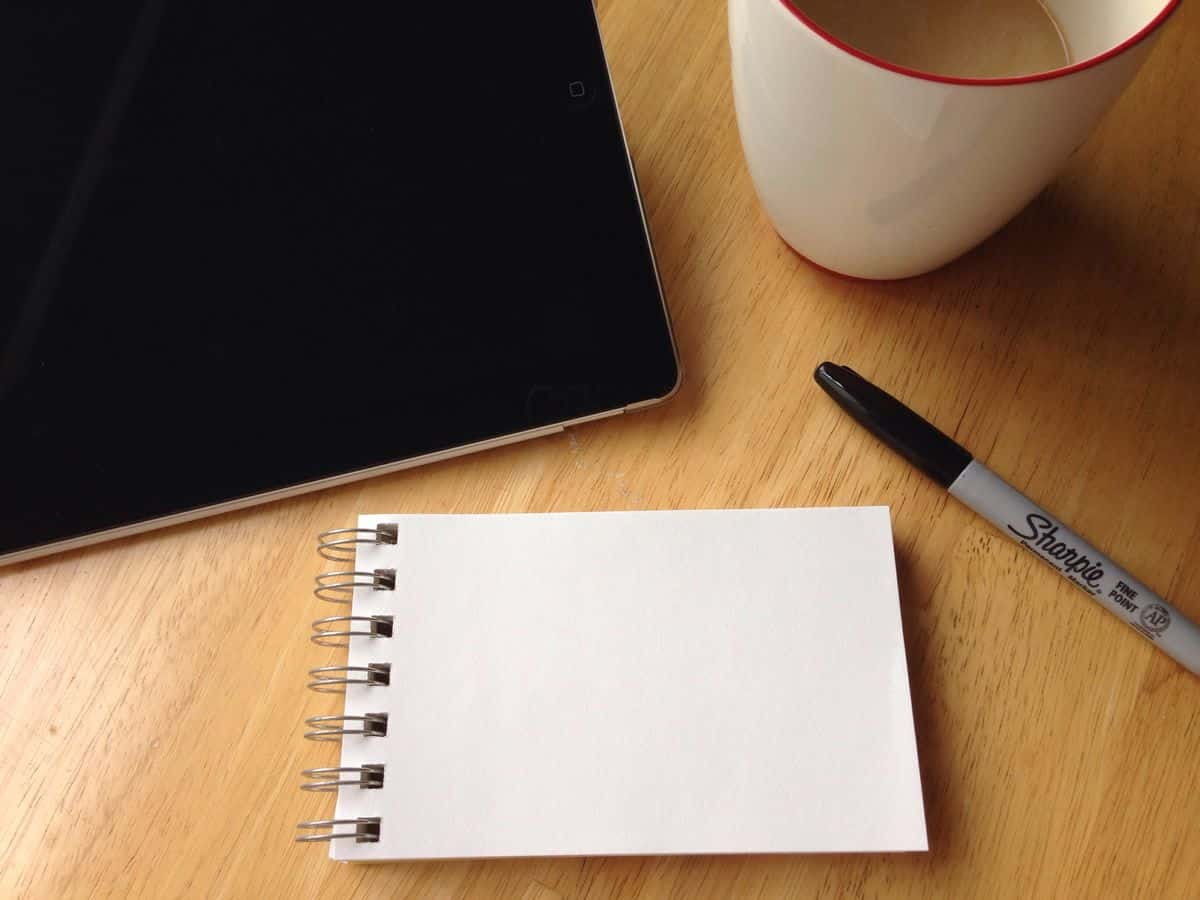 A close-up of a small notepad, marker, tablet computer and coffee on a desk. For initial brainstorming, a pen and paper may be your best UX design tools.