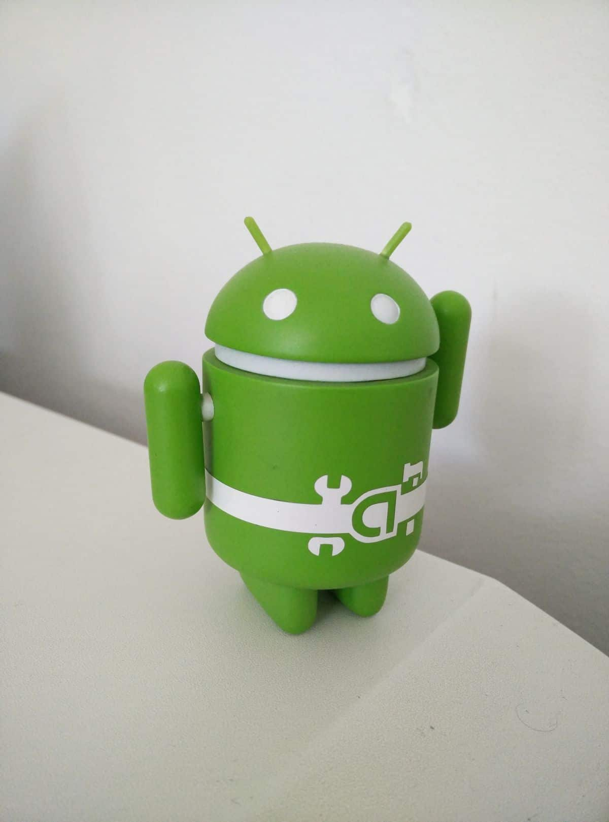 A small, green plastic Android figurine lifts one arm as though waving.