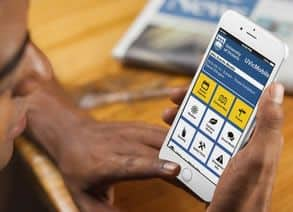 A close-up of a young man holding a smartphone displaying an AppArmor app, the mobile UI design tailored to the needs of his university.